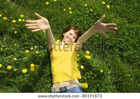 young girl in yellow shirt lying on grass, smiling and stretching her hands to camera
