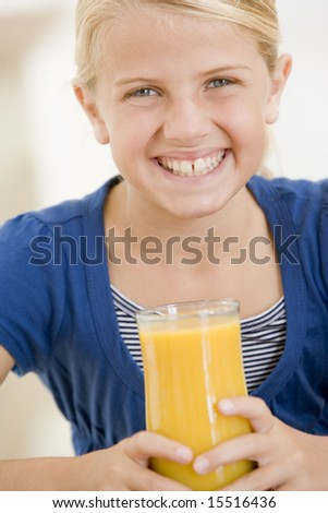 Young girl indoors drinking orange juice smiling - stock photo