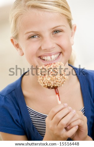 Young girl indoors eating candy apple smiling - stock photo