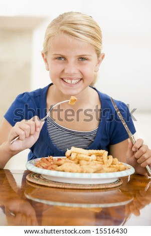 Young girl indoors eating fish and chips smiling