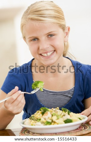 Young girl indoors eating pasta with brocoli smiling - stock photo
