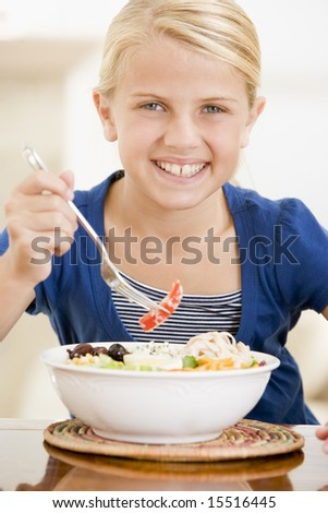 Young girl indoors eating seafood smiling - stock photo