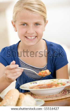 Young girl indoors eating soup smiling - stock photo