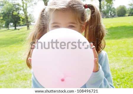 Young girl inflating a pink balloon in front of her face in the park on a sunny day. - stock photo