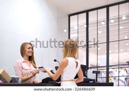 Young girl is at the checkout in the store - stock photo