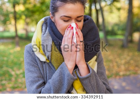 Young girl is blowing her nose. She is cold. Autumn time