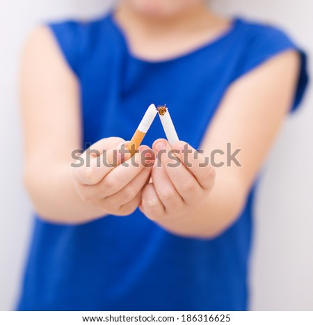 Young girl is breaking a cigarette, quit smoking concept - stock photo