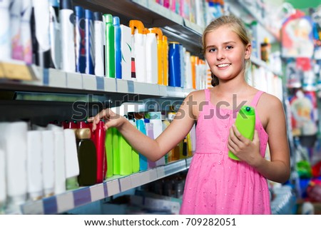 Young girl is choosing shampoo in the supermarket.