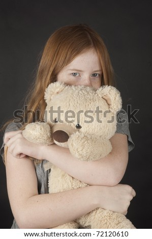 young girl is cuddling with a teddybear - stock photo