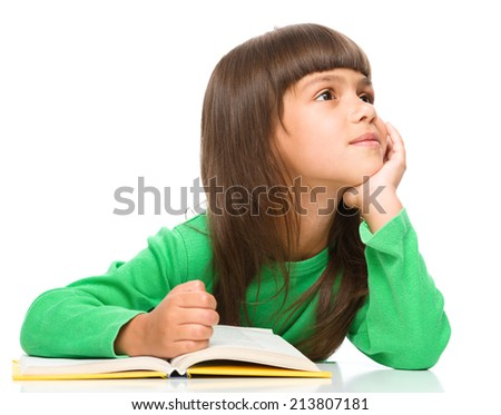 Young girl is daydreaming while reading book, isolated over white - stock photo