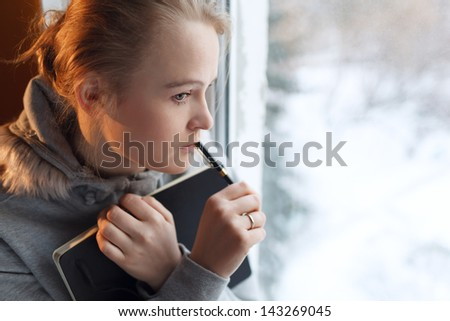 Young girl is dreaming by the window with notebook and pen - stock photo