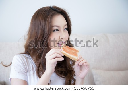 Young girl is eating fresh toast