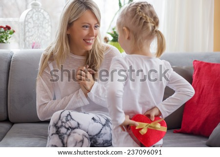 Young girl is giving present to her mother - stock photo