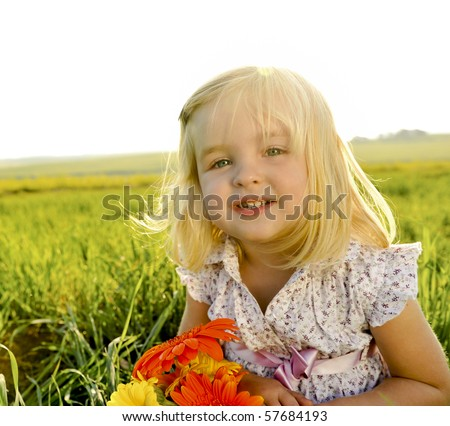 Young girl is happy outside, lens flare from the sun behind her head - stock photo
