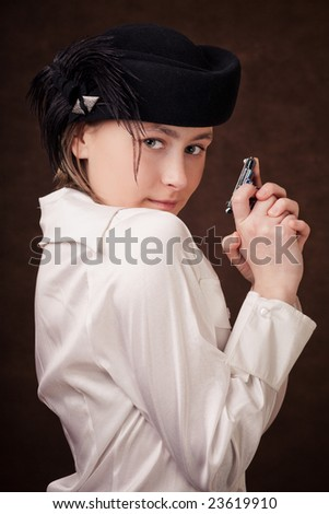 Young girl is holding a toy pistol in hands