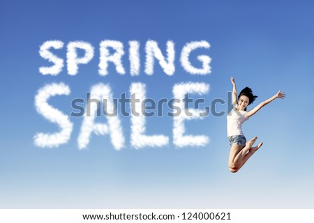 Young girl is jumping beside spring sale shape clouds under blue sky - stock photo