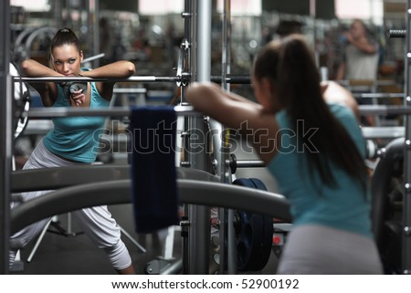 Young girl is looking at the mirror on sport training in a gym - stock photo