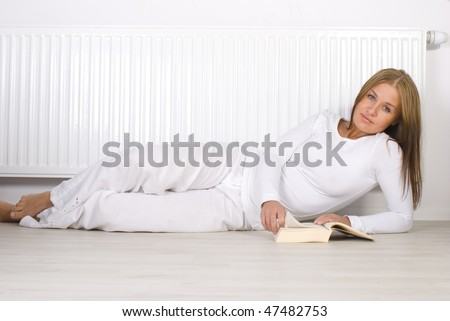 Young girl is lying by a white heater - stock photo