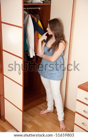 Young girl is making choice near wardrobe