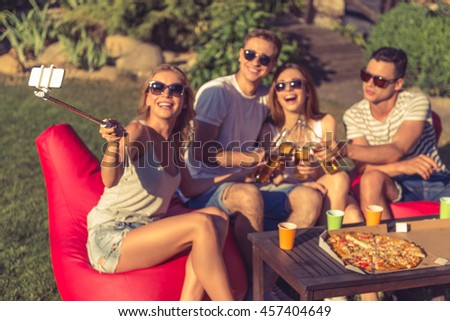 Young girl is making selfie with her friends who are clinking bottles of beverage and smiling, sitting on bean bag chairs outdoors. Phone and monopod in focus - stock photo