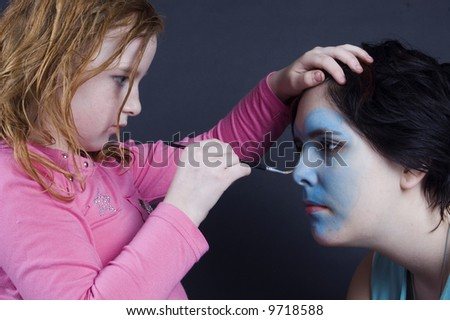 young girl is painting females face - stock photo