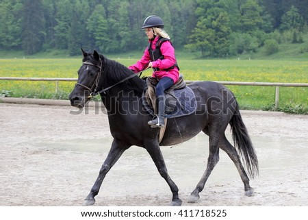 young girl is practicing horse riding on a course