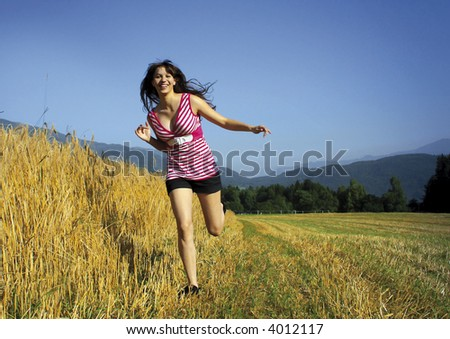 young girl is running/jumping beside a cornfield. Unique keyword for this collection: happy77