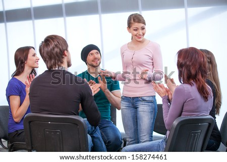 Young girl is shearing her thoughts in a group of people. All clapping  - stock photo