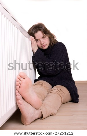 young girl is sitting by a white heater