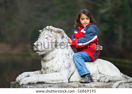 Young girl is sitting on the top of the lion sculpture with leopard toy in her pocket - stock photo