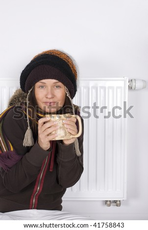 Young girl is standing by a white heater - stock photo