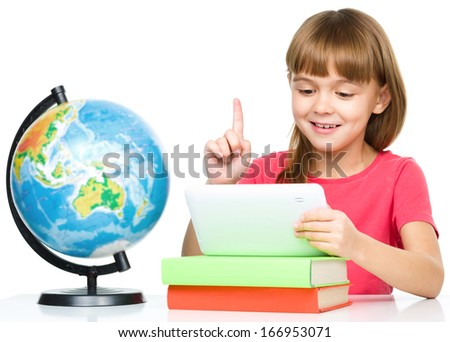 Young girl is using tablet and pointing up while studying geography, isolated over white - stock photo