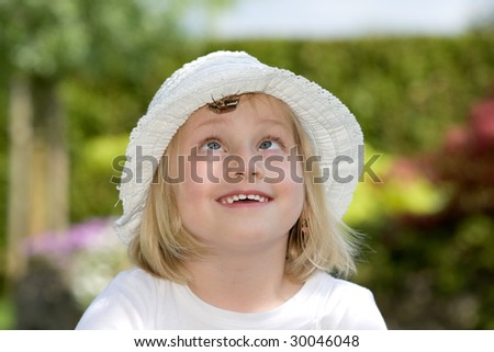 Young girl is watching a chafer beetle on her hat - stock photo