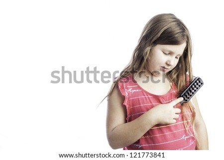 Young girl isolated on white brushing her long hair - stock photo