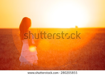 young girl joys on the wheat field at the sunset time