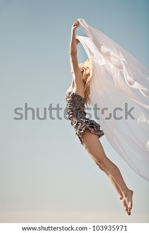 Young girl jumping in blue sky with smile - stock photo