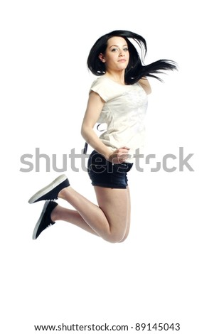 Young girl jumping in the air against white background - stock photo