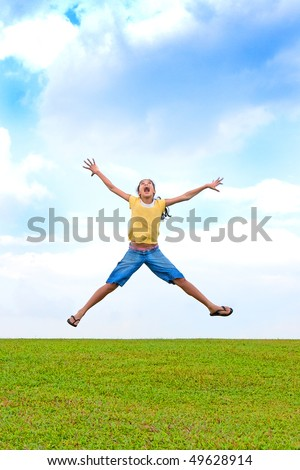 Young girl jumping in the air, over green field - stock photo
