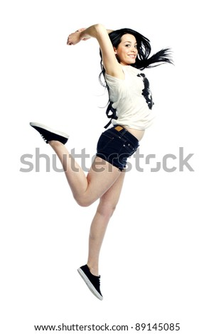Young girl jumping in the air smiling against white background - stock photo