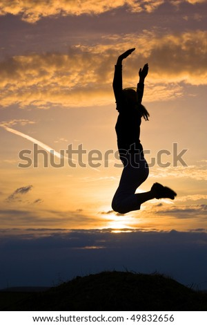 Young girl jumping in the sunset. - stock photo