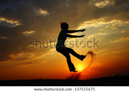 Young girl jumping in the sunset silhouette