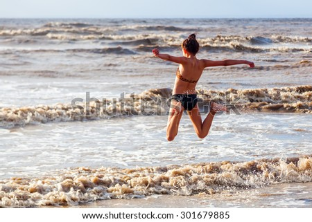 young girl jumping in the water of the sea at a beach in Somerset, England - stock photo