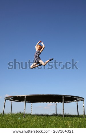 Young girl jumping on a trampoline on green meadow - stock photo