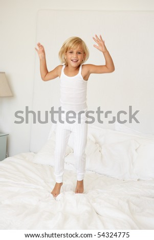 Young Girl Jumping On Bed - stock photo