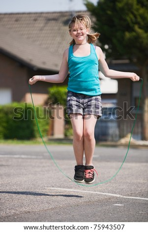 Young girl jumping rope outdoors - stock photo