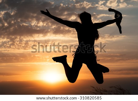 Young girl jumping silhouette with shawl on background of beautiful cloudy sky with orange sunset and rays of light