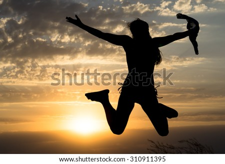 Young girl jumping silhouette with shawl on background of beautiful cloudy sky with yellow sunset and rays of light