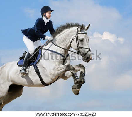 Young girl jumping with dapple-grey horse - stock photo