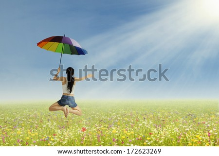 Young girl jumping with umbrella on the park - stock photo