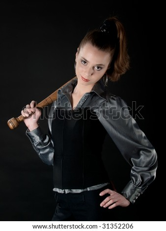 Young girl keeps baseball bat on hers shoulder and smirks - stock photo